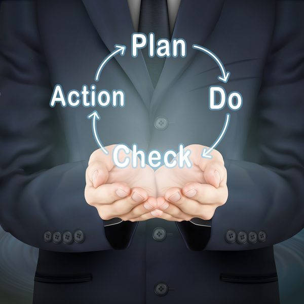 close-up look at businessman holding PDCA word